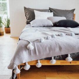 szara narzuta na łóżko z frędzlami